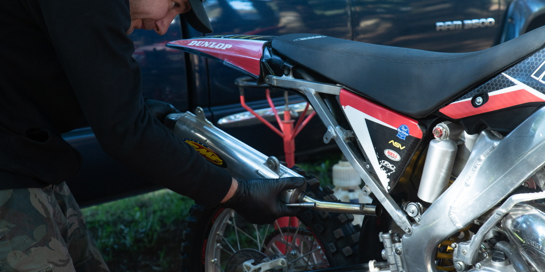 Mechanic installing muffler on dirt bike
