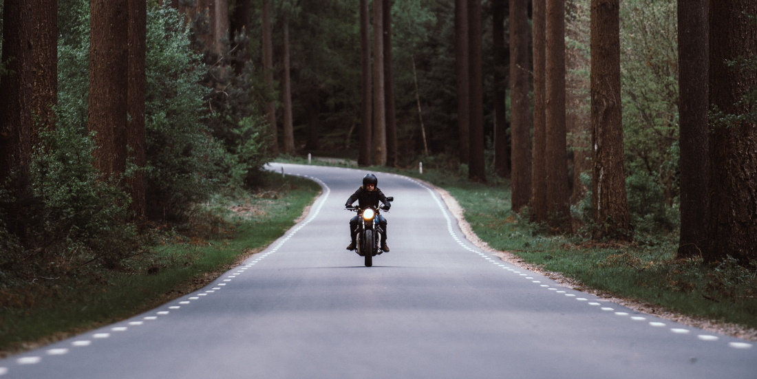 Rider on motorcycle through woods on a long road