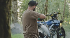 Guy spraying a dirt bike with water