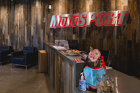 MotoSport reception area with distressed wood walls and desk