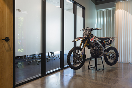 A motocross motorcycle displayed in the reception area of the MotoSport office